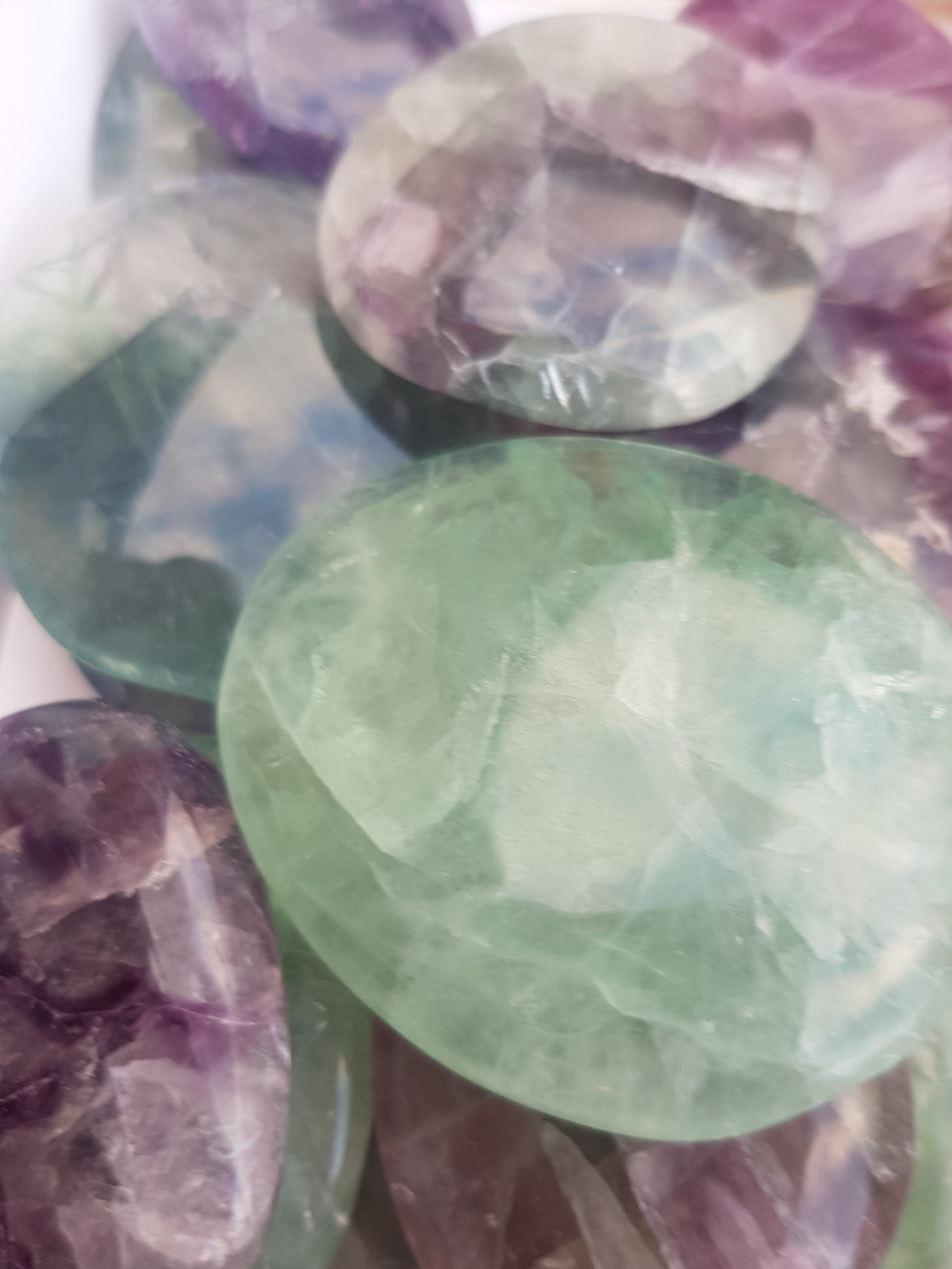 Rainbow fluorite palmstones. translucent flat and smooth. colour varies from green to purple in a single piece