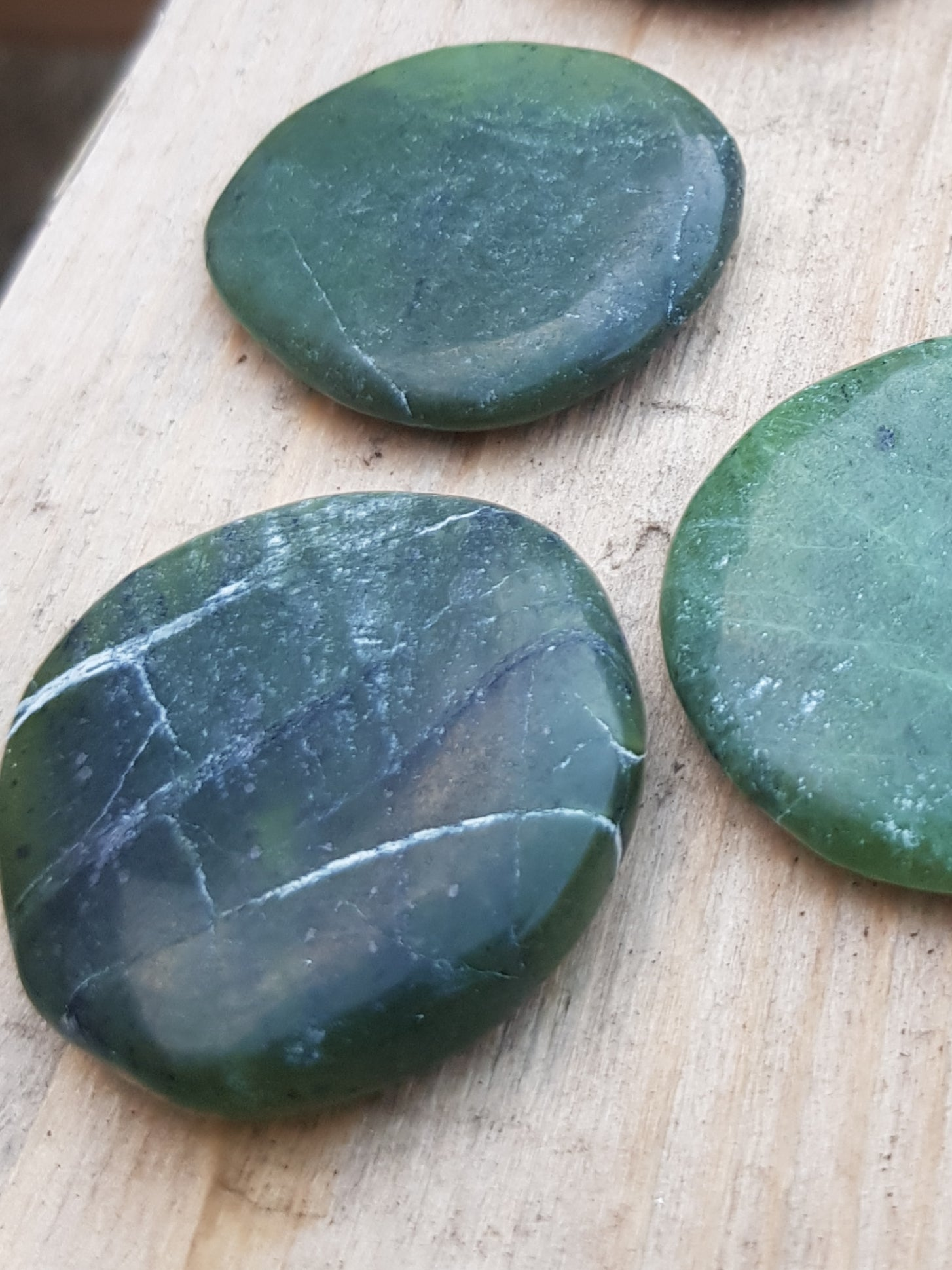 nephrite jade palmstone. dark green with some white lineations.