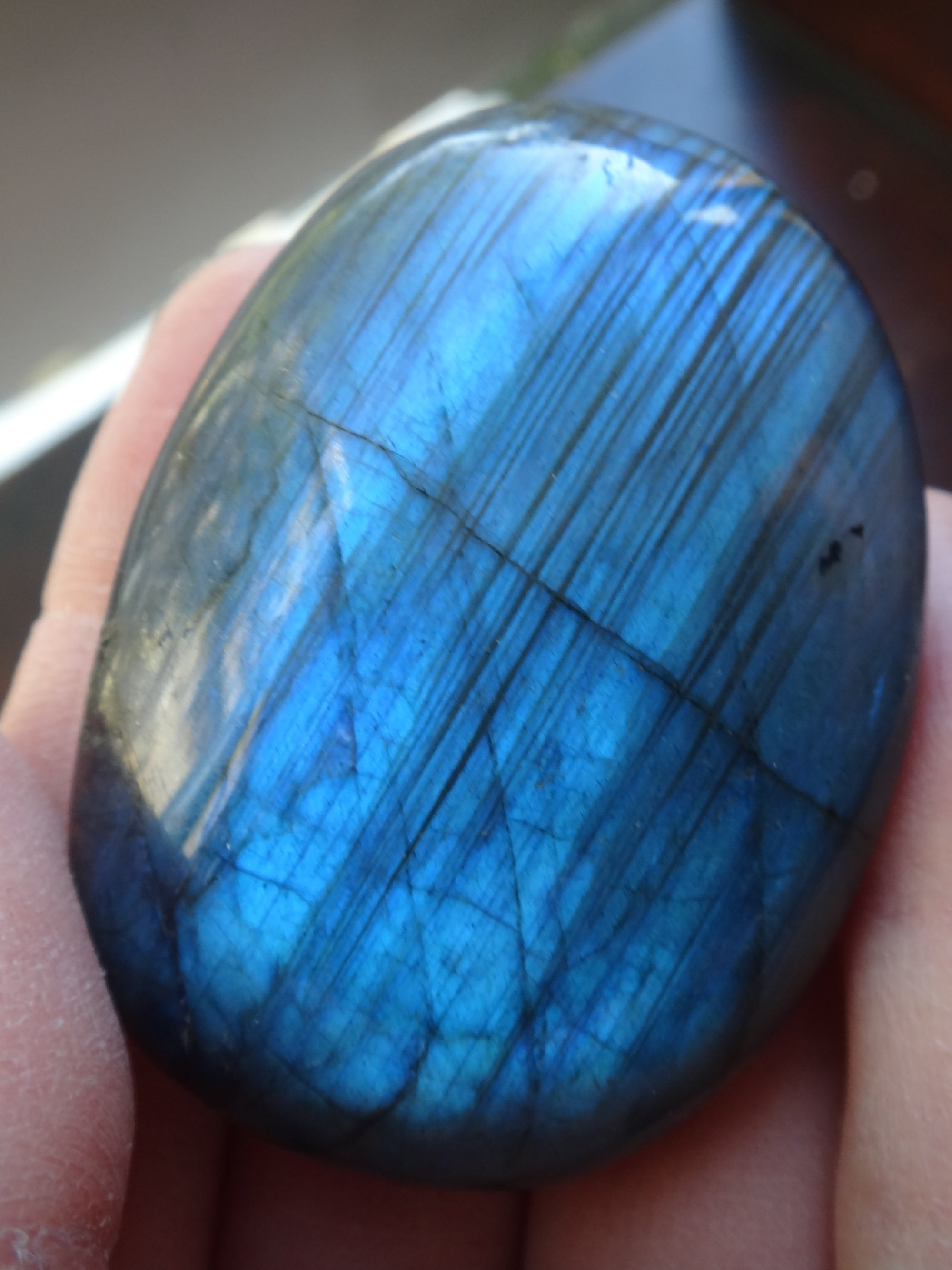 a labradorite palmstone held in a hand. The piece has blue labradorescence. It is showing distinct lamella twinning