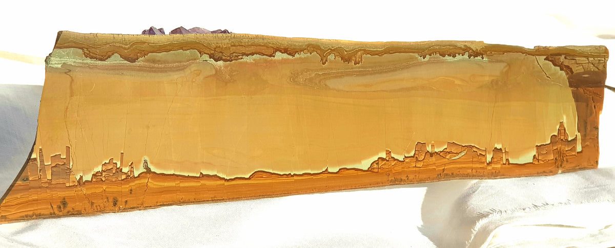 a polished slice of ruin marble. the piece is in shades of brown. the bottom of the image looks like a painted city, but is natural to the stone