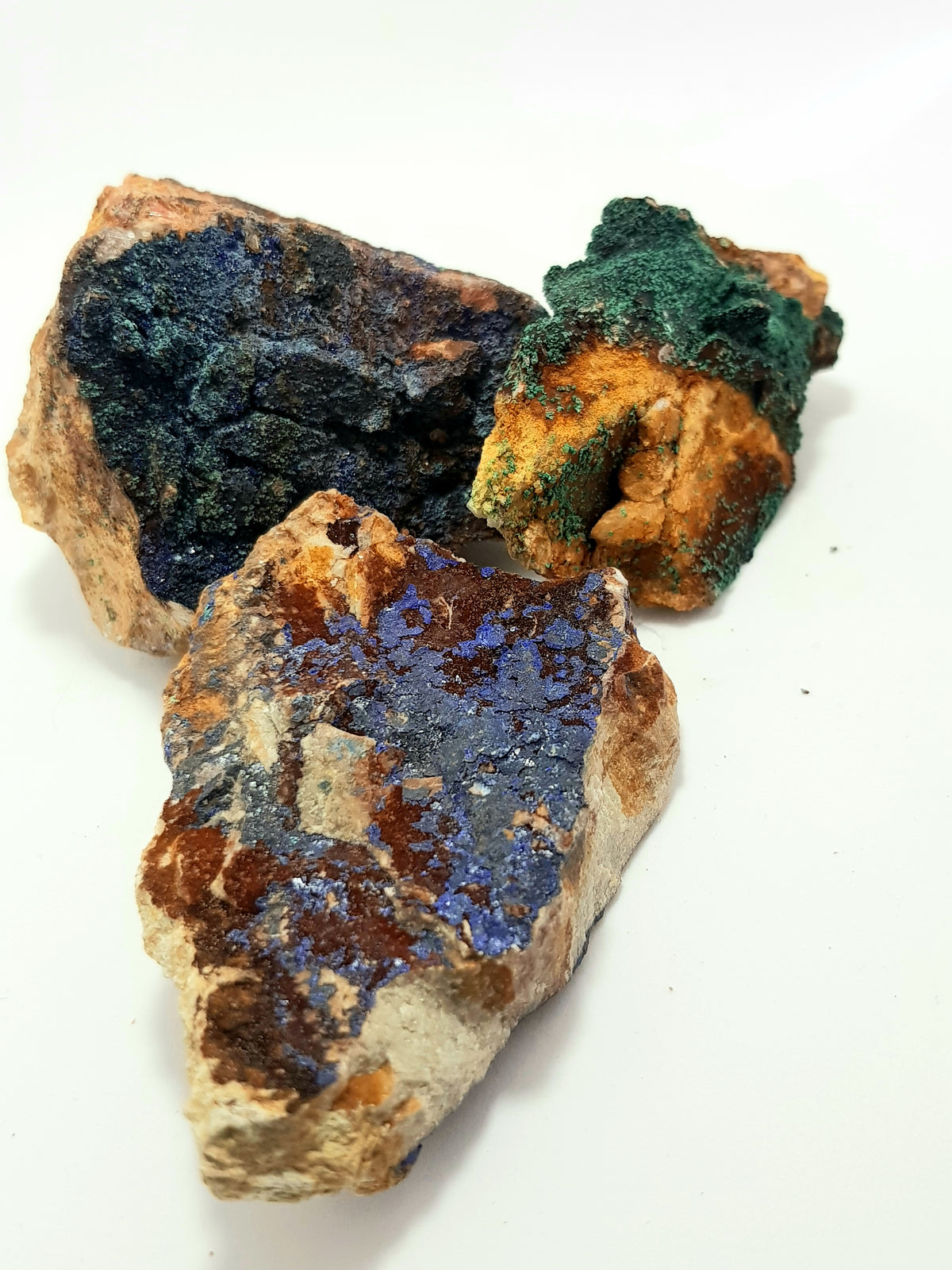 three pieces of raw azurite and malachite on the matrix. vibrant blue and green crystals on a beige carbonate matrix