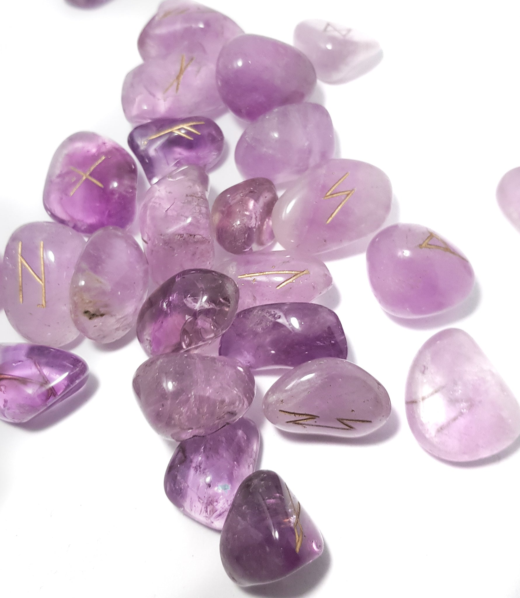 scattered set of amethyst rune stones. The pieces are purple the runic inscriptions are gold. -- science of magic