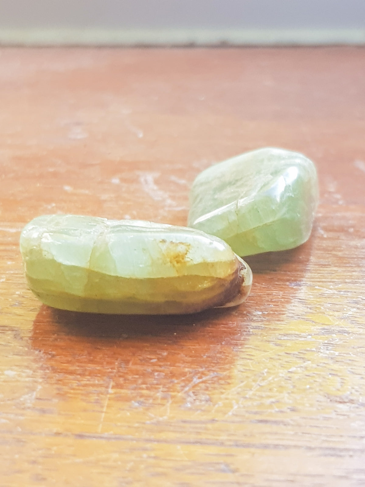 two green aquamarine tumblestones or a dark wood grained surface