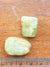 two green aquamarine tumblestones. They are placed against a ruler for scale. They are about 2.5cm long.
