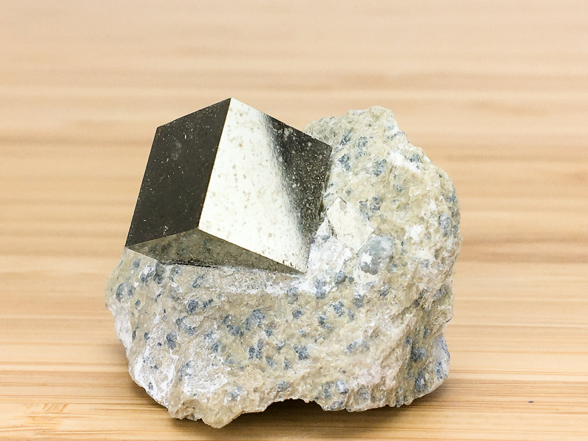 Naturally occurring iron pyrite cubic crystal in matrix
