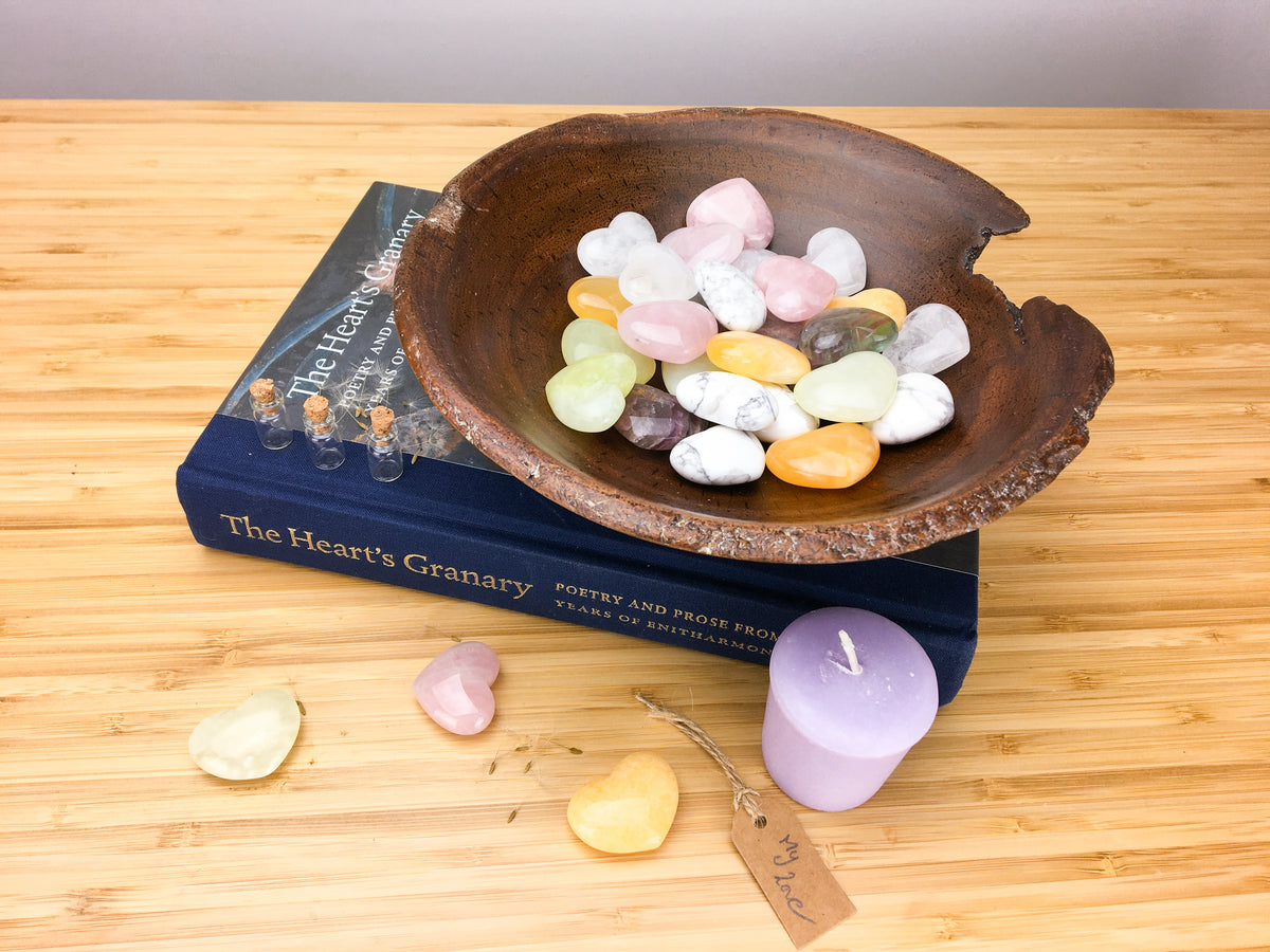 A hand carved wooden bowl filled with pastel coloured carved stone hearts. The bowl stands on top of a book called the hearts granary. The book is sitting on a light wood grained surface. A purple candle, three hearts and a table saying my love is also lying on this surface.