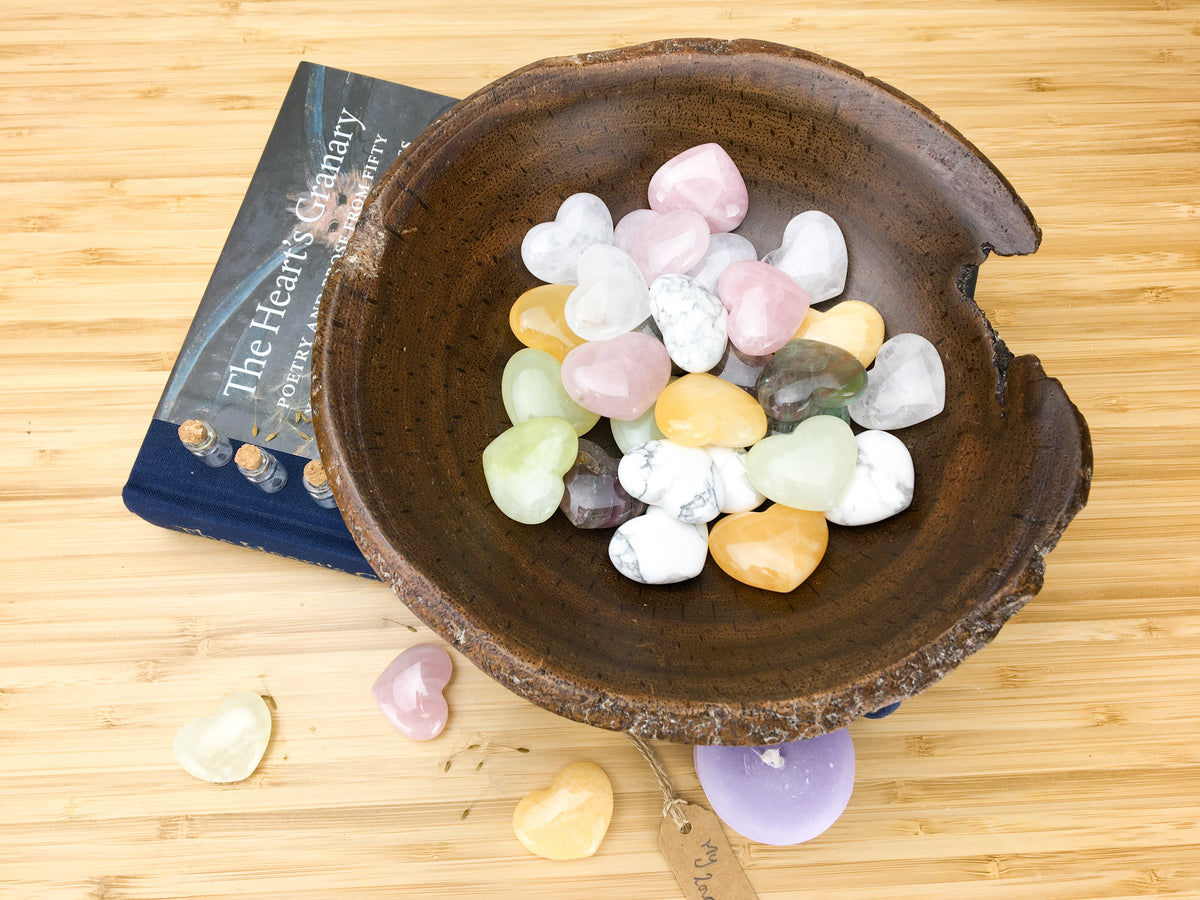 "A hand carved wooden bowl filled with pastel coloured carved stone hearts. The bowl stands on top of a book called the hearts granary. The book is sitting on a light wood grained surface. A purple candle, three hearts and a lable saying ""my love"" is also lying on this surface."