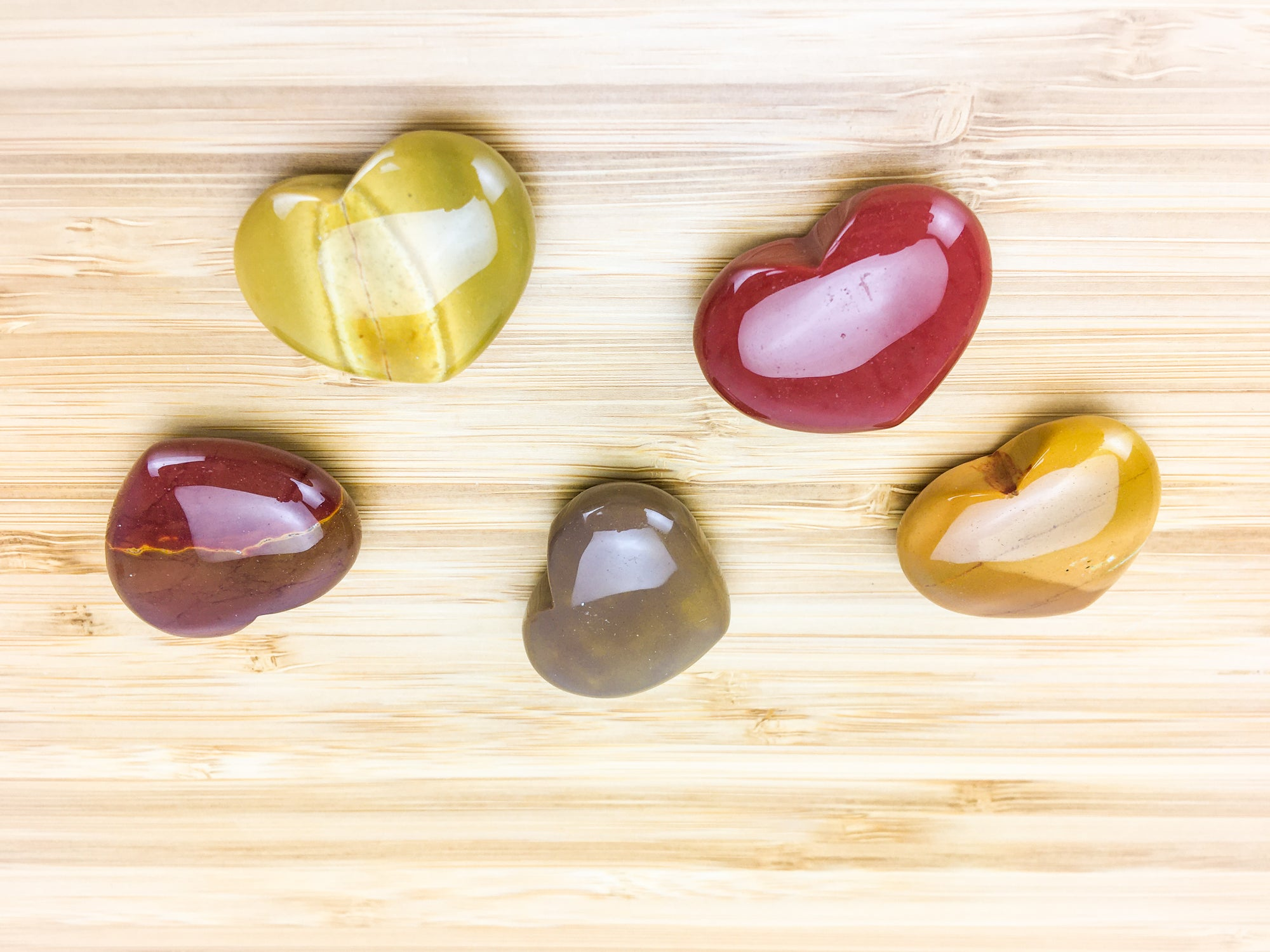 Five mookaite hearts on a grained wood table. The moojaite shows intense colour variation. Some pieces are red and some are orange