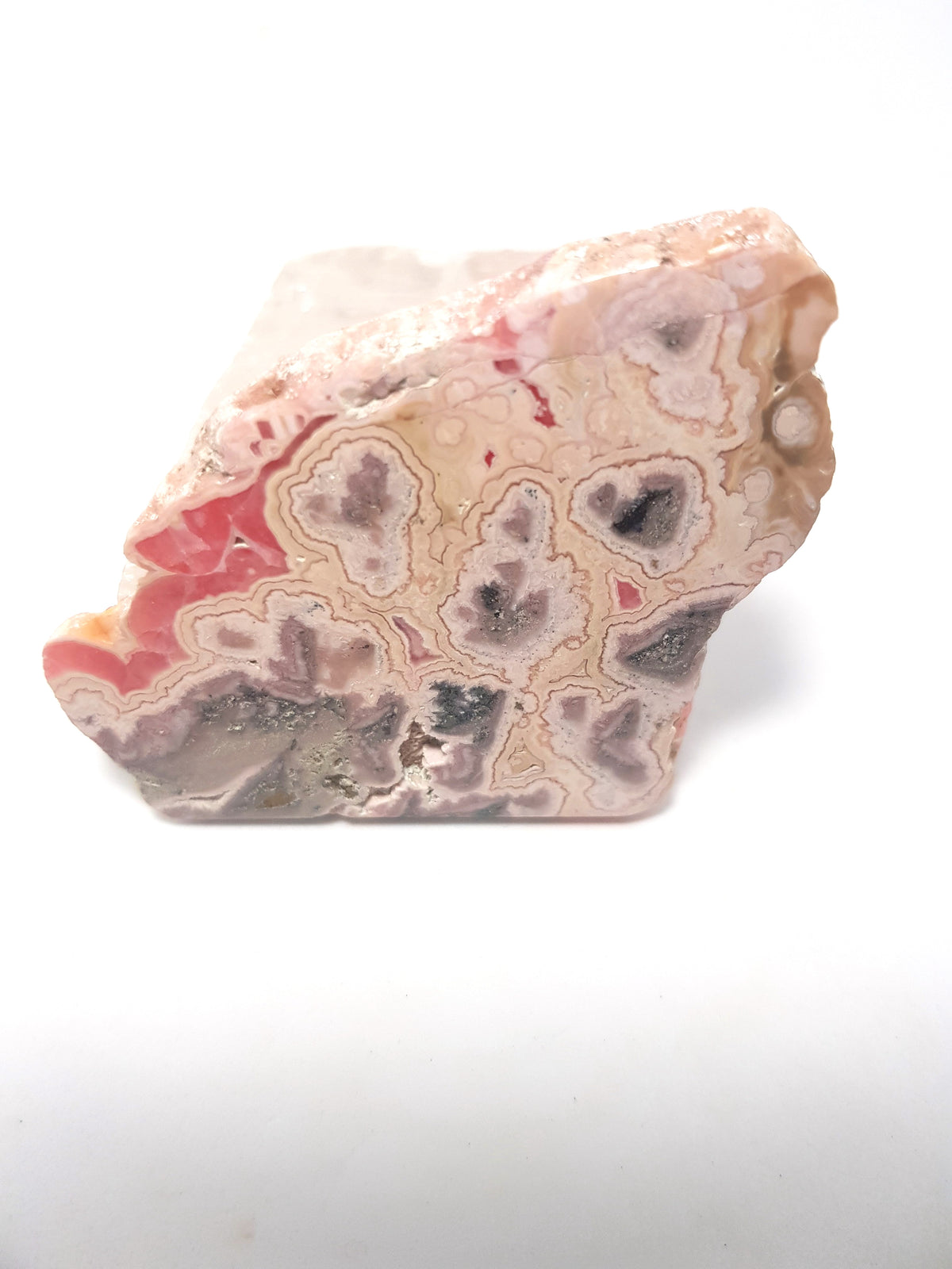 polished slice of rhodochrosite. This consists of bands of pink materials. The colours range from a deep pink to a pink tinted grey.