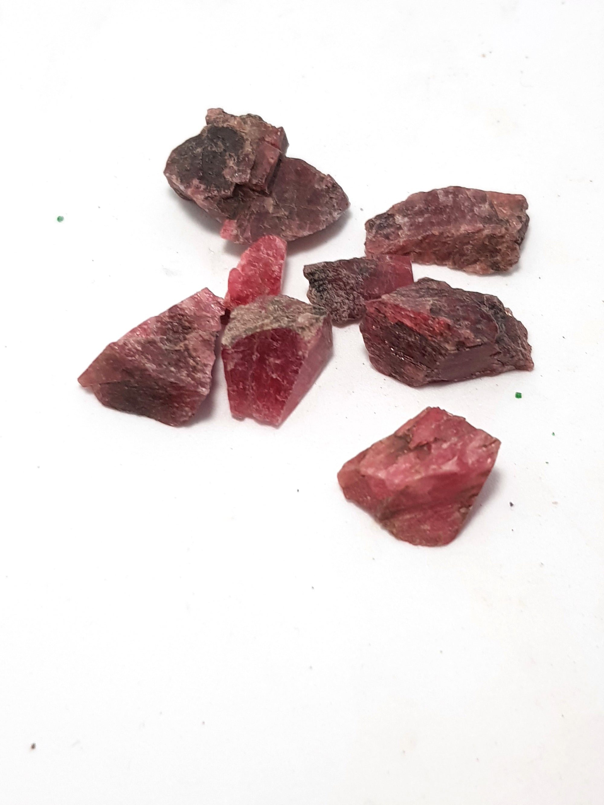 raw chips of rhodonite. They are a very dark pink.