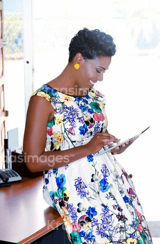 Businesswoman using a digital tablet while standing in front of windows in office stock photo