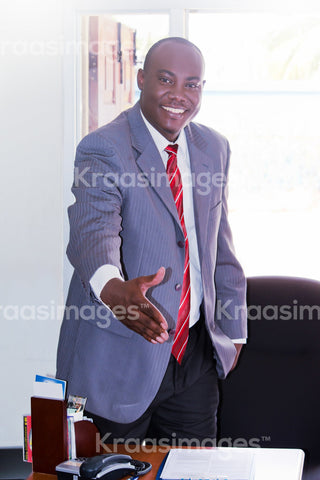 Positive mature businessman ready to give handshake in office.