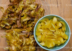 Peeled jackfruit and seeds on a wooden table with fresh jackfruit in a bowl stock photo