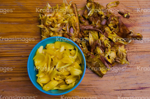Peeled jackfruit and seed on wooden background with fresh jackfruit in a bowl stock photo