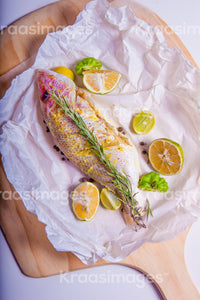 Top view of tasty snapper fish with herbs, limes and spices stock photo