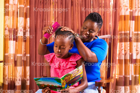 Little girl reading a book as mother styles her hair