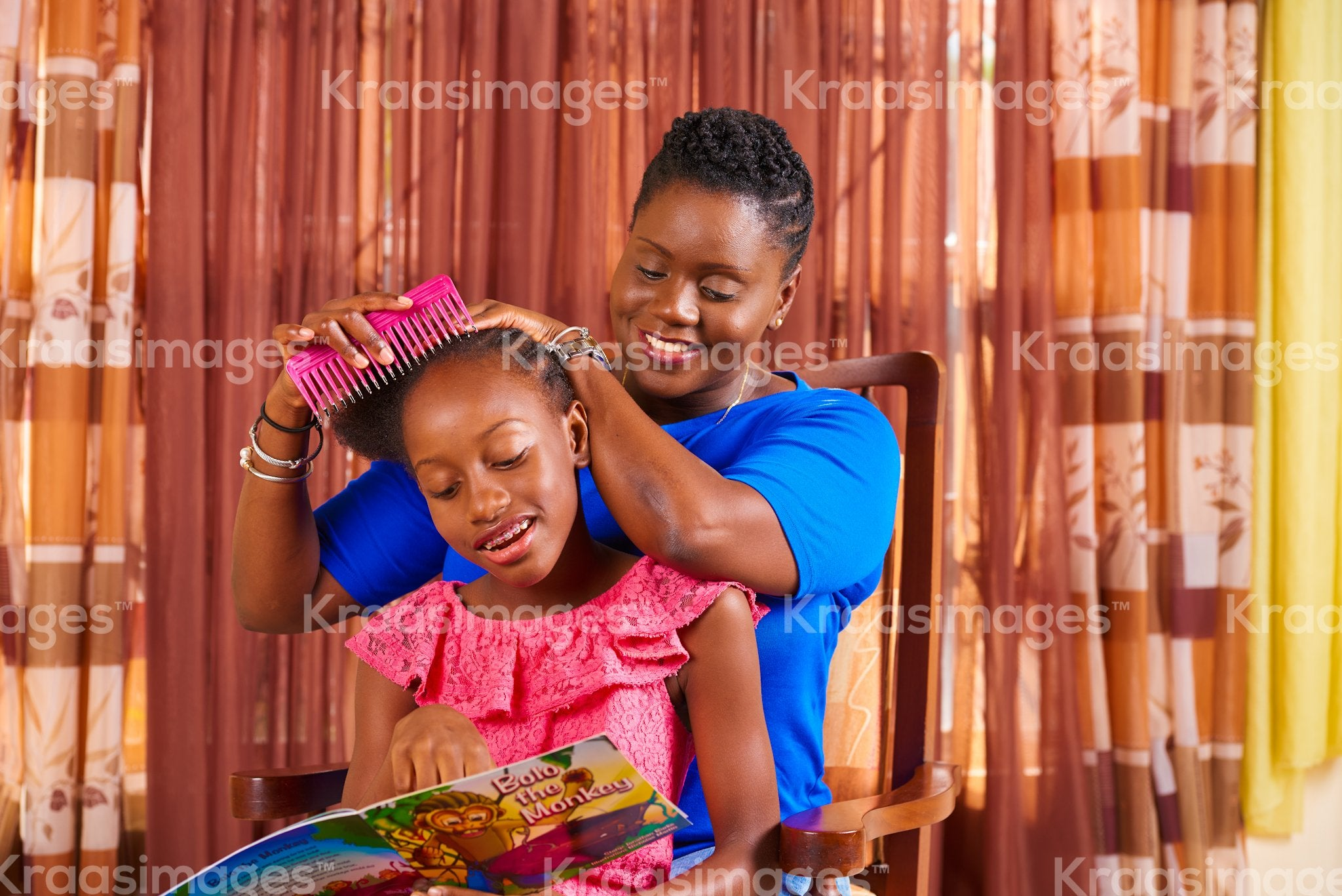 Daughter reading as mother combs her hair stock photo