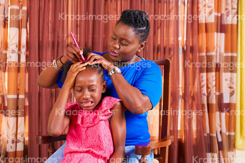 Child wincing as her mother styles her hair stock photo