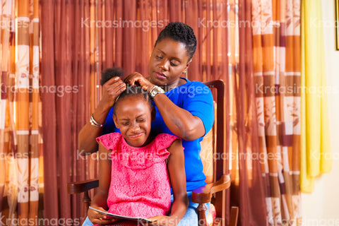 Child wincing as her hair gets combed