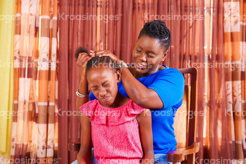 Child wincing as her hair is being styled stock photo