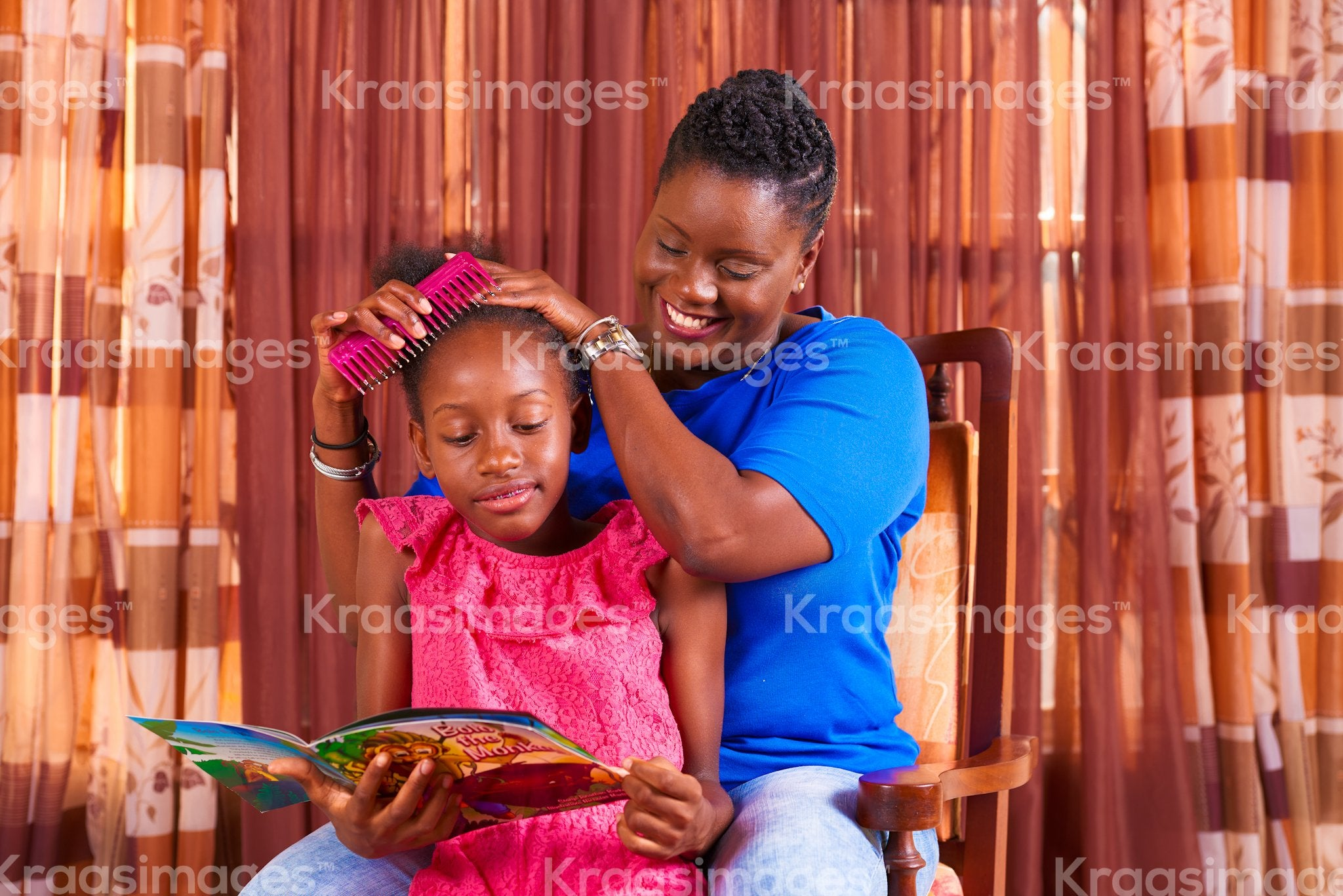 Daughter reading as mom combs her hair stock photo