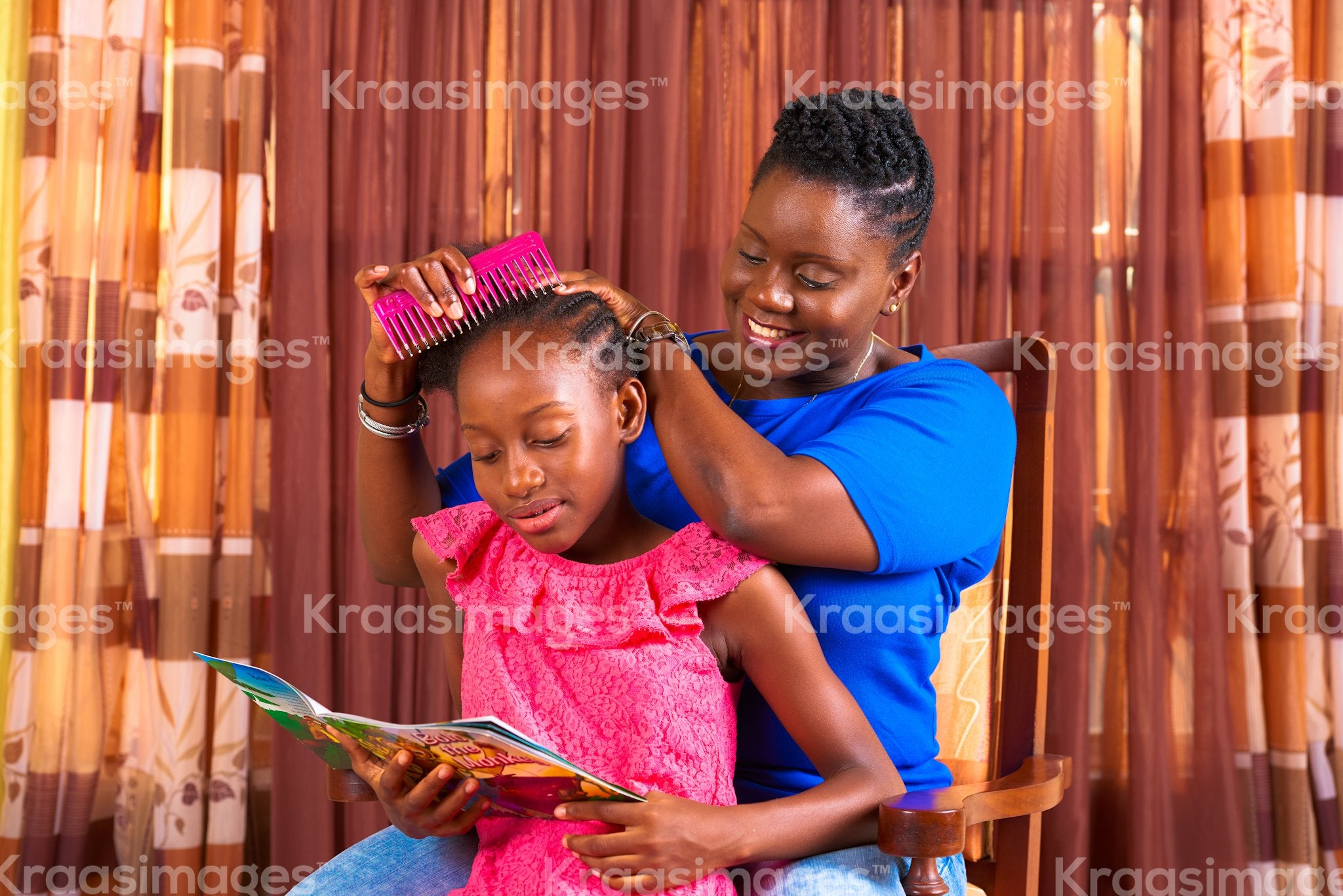 Little girl reading as mom styles her hair stock photo