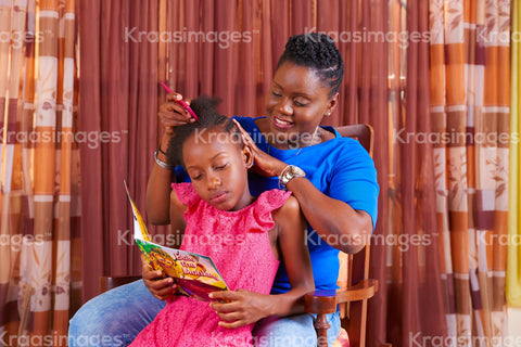 Child reads while her mom styles her hair stock photo