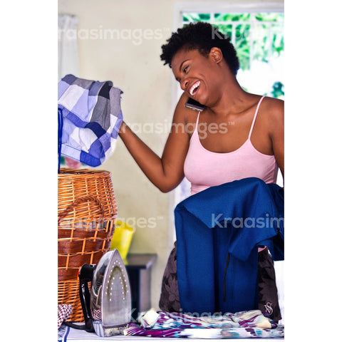 Woman on the phone while doing chore