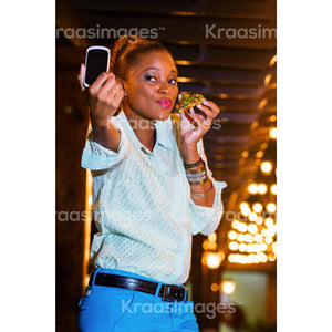 Woman taking selfie with food in her hand stock photo