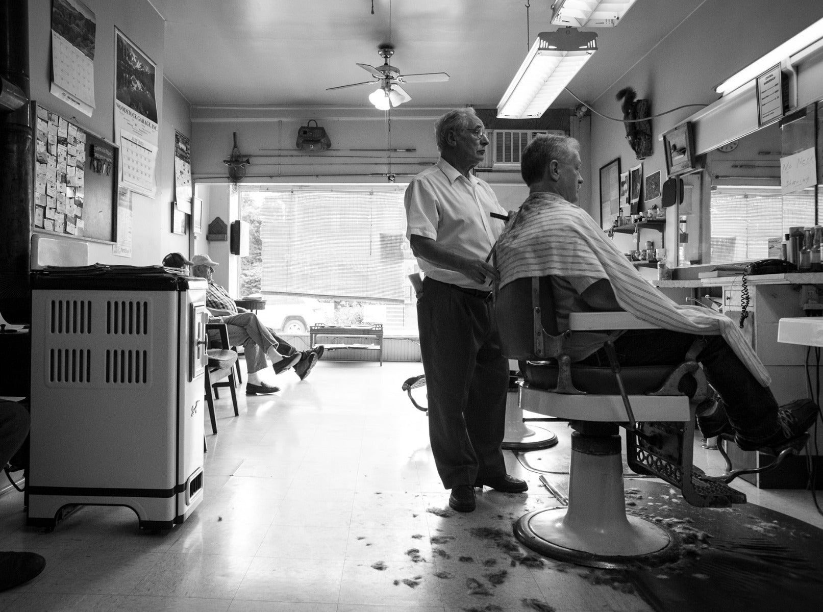 Man getting a haircut in a barbershop with barber