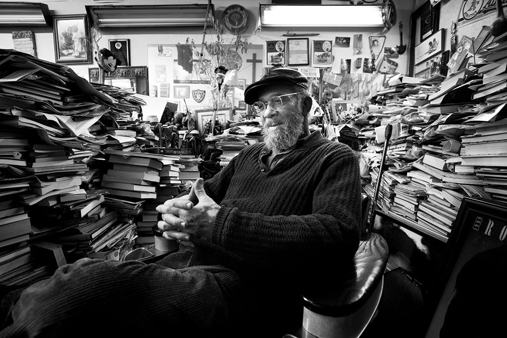 Man sitting in barber chair surrounded by books