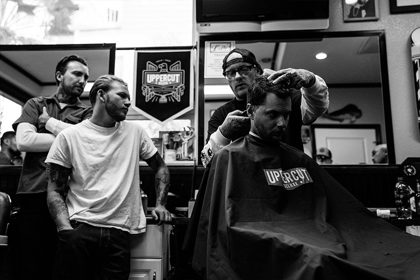 Barber cutting hair while others watch