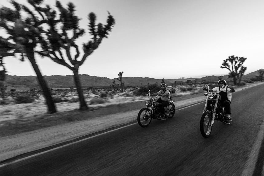 Two men riding motorbikes down a highway