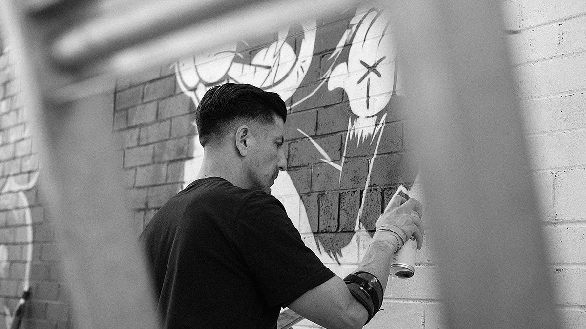Man using spray paint can on wall