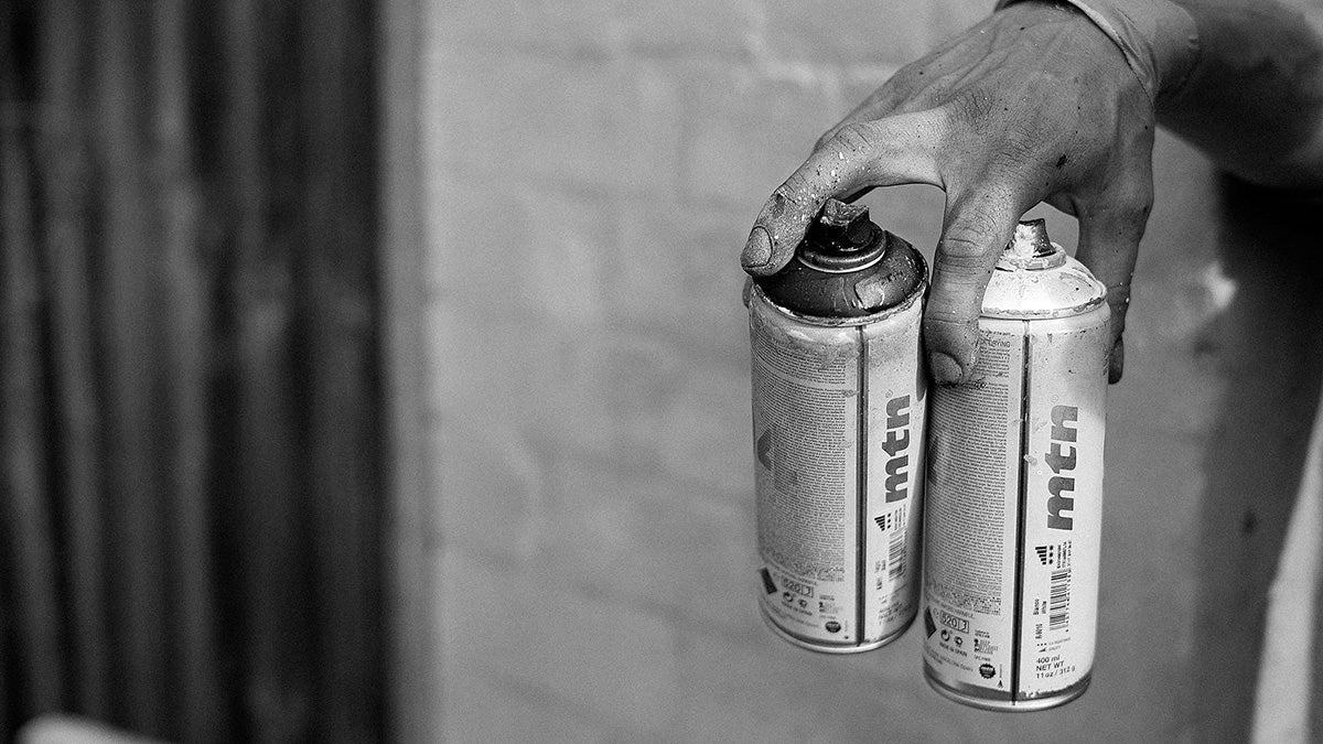 Hand holding spray paint cans