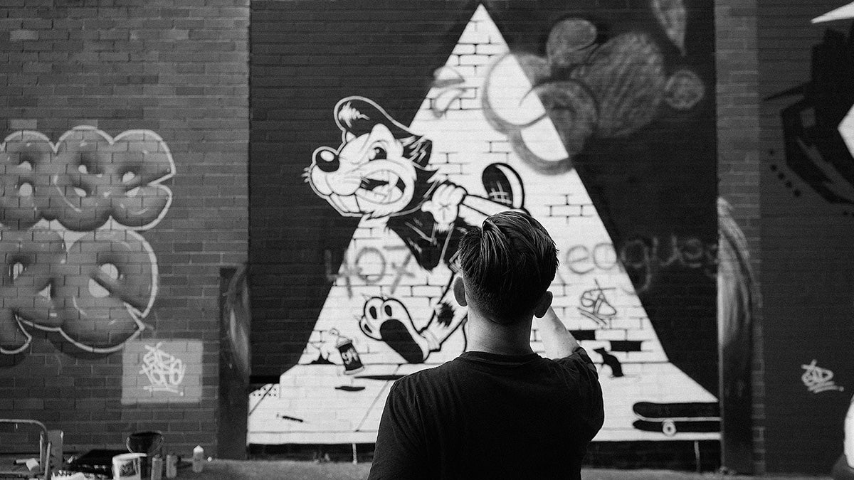 Man standing in front of grafitti wall