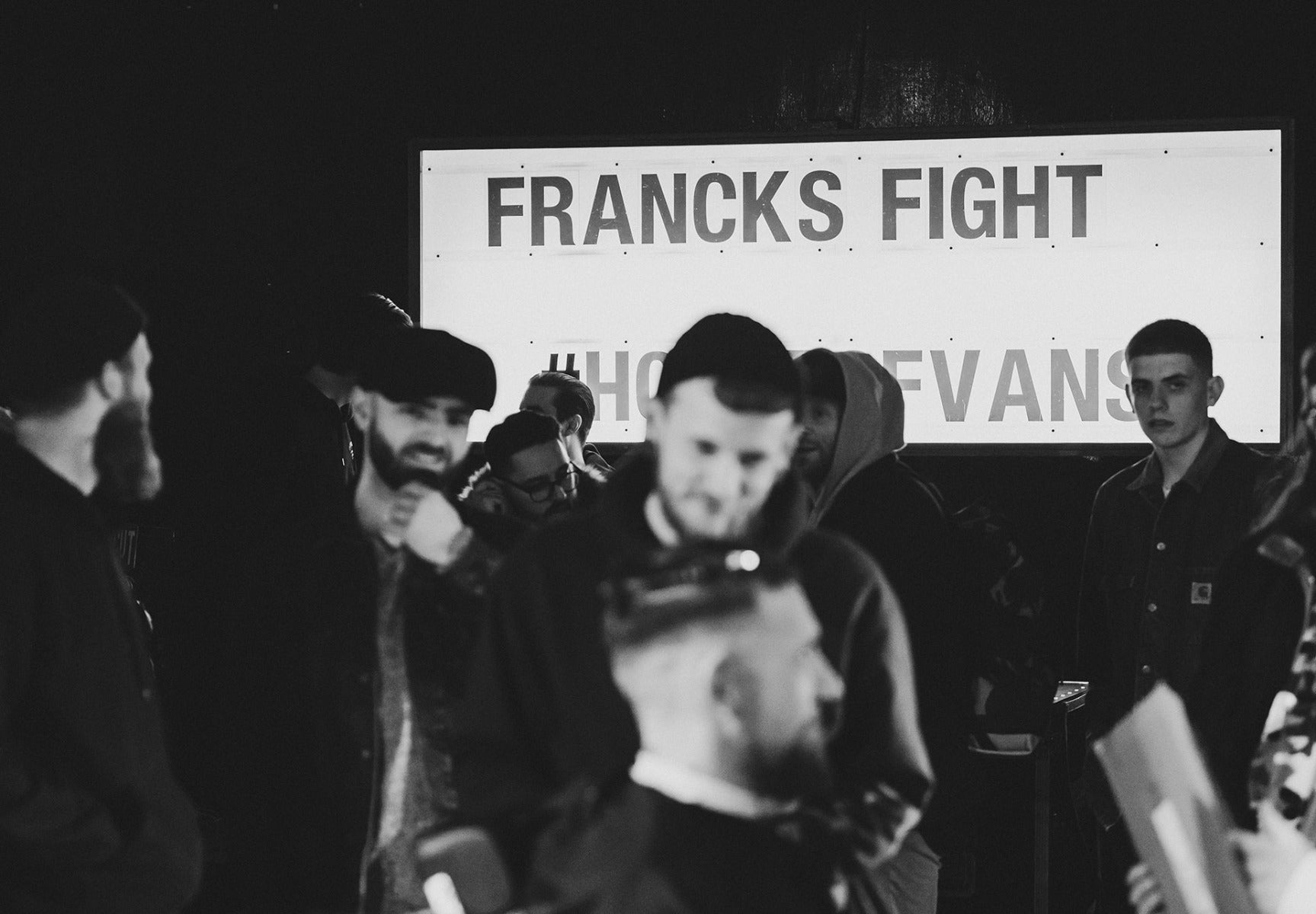 Group of people with Francks Fight sign in the background