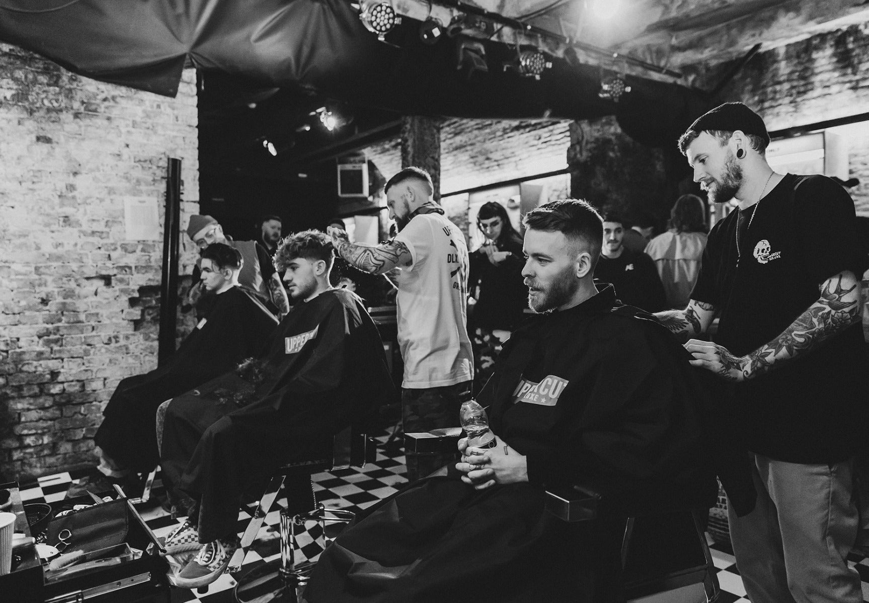 Men in barberchairs getting haircuts