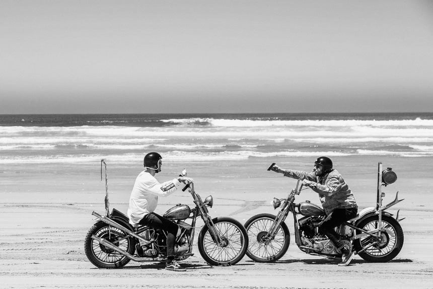 Two men talking to each other while sitting on motorbikes on the beach