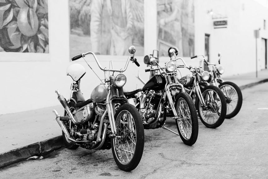 Four motorbikes lined up against a wall
