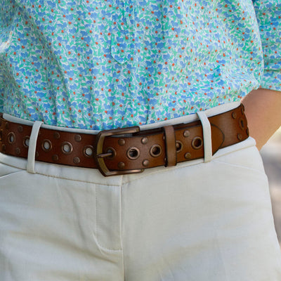 Nickel free brown leather belt with bronze colored buckle, grommets, and studs