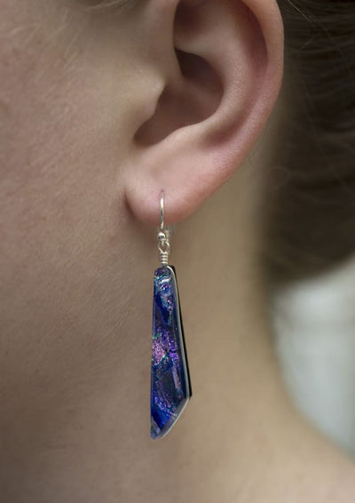 Model is shown wearing Queen Falls Nickel Free Earrings - lilac and purple dichroic glass in comet shaped dangle