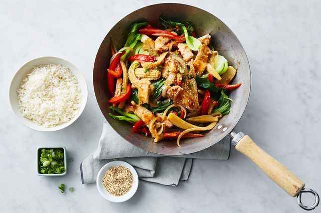 Pork Fillet stir fry recipe in a wok and condiments on grey background