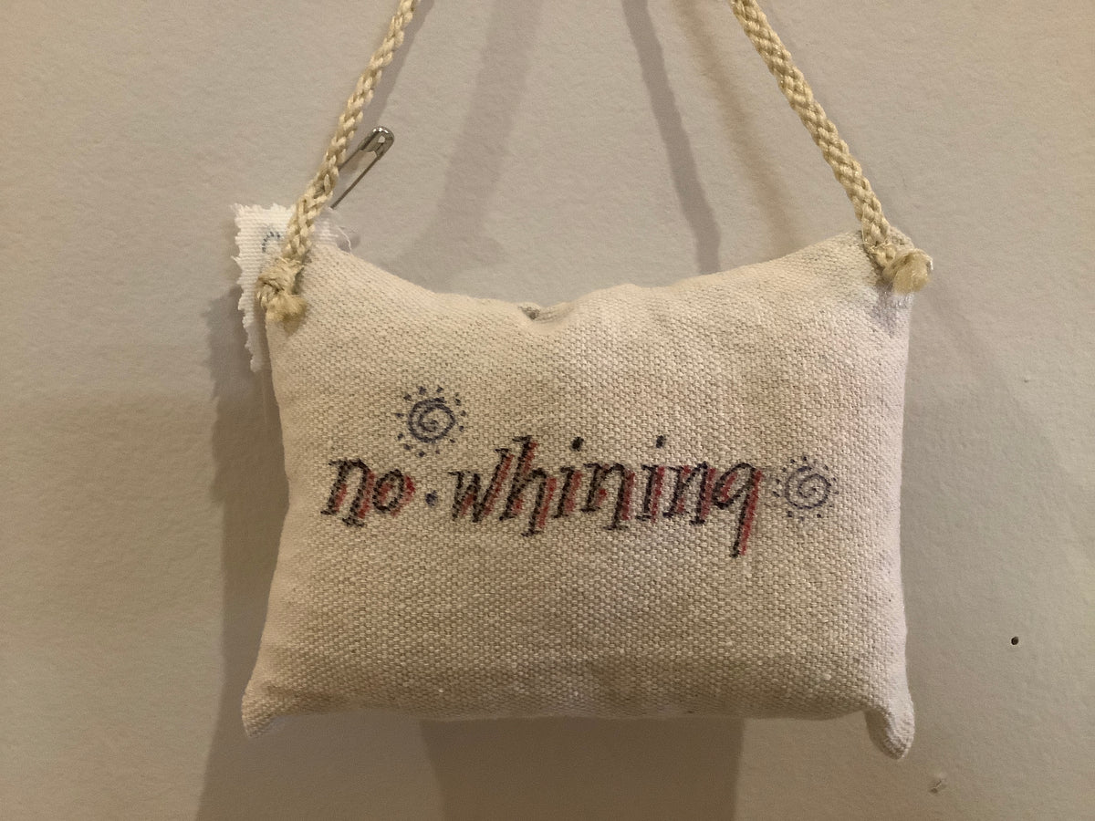 Small hanging pillow with written phrase
