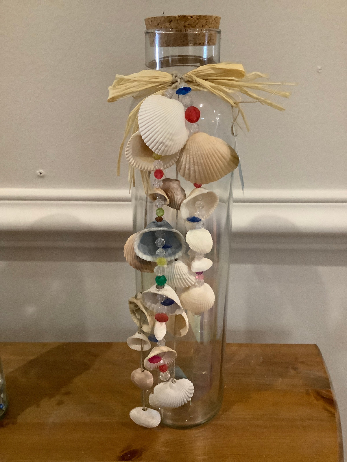 Tall glass bottle with shell garland