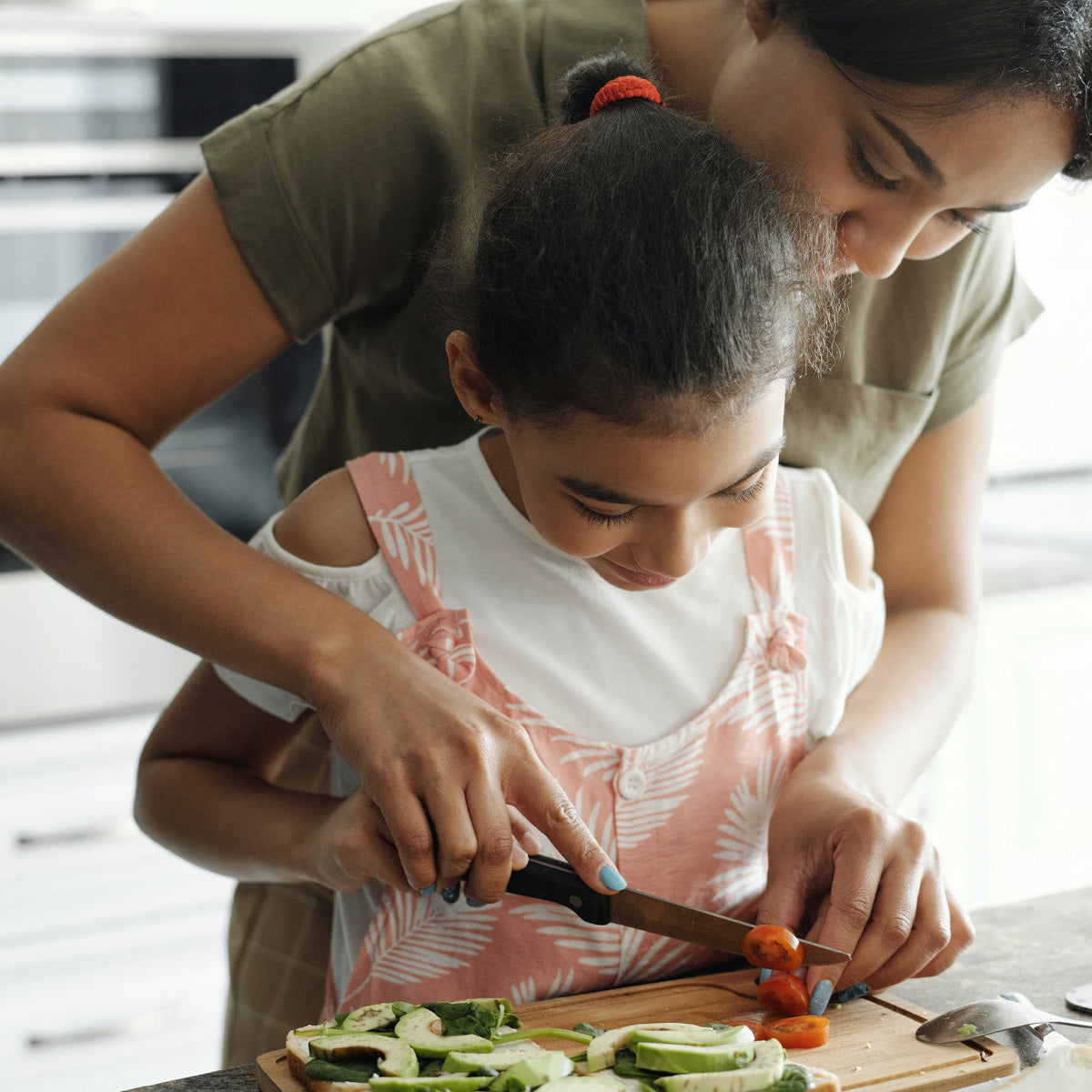 mother and child chopping vegetables in kitchen