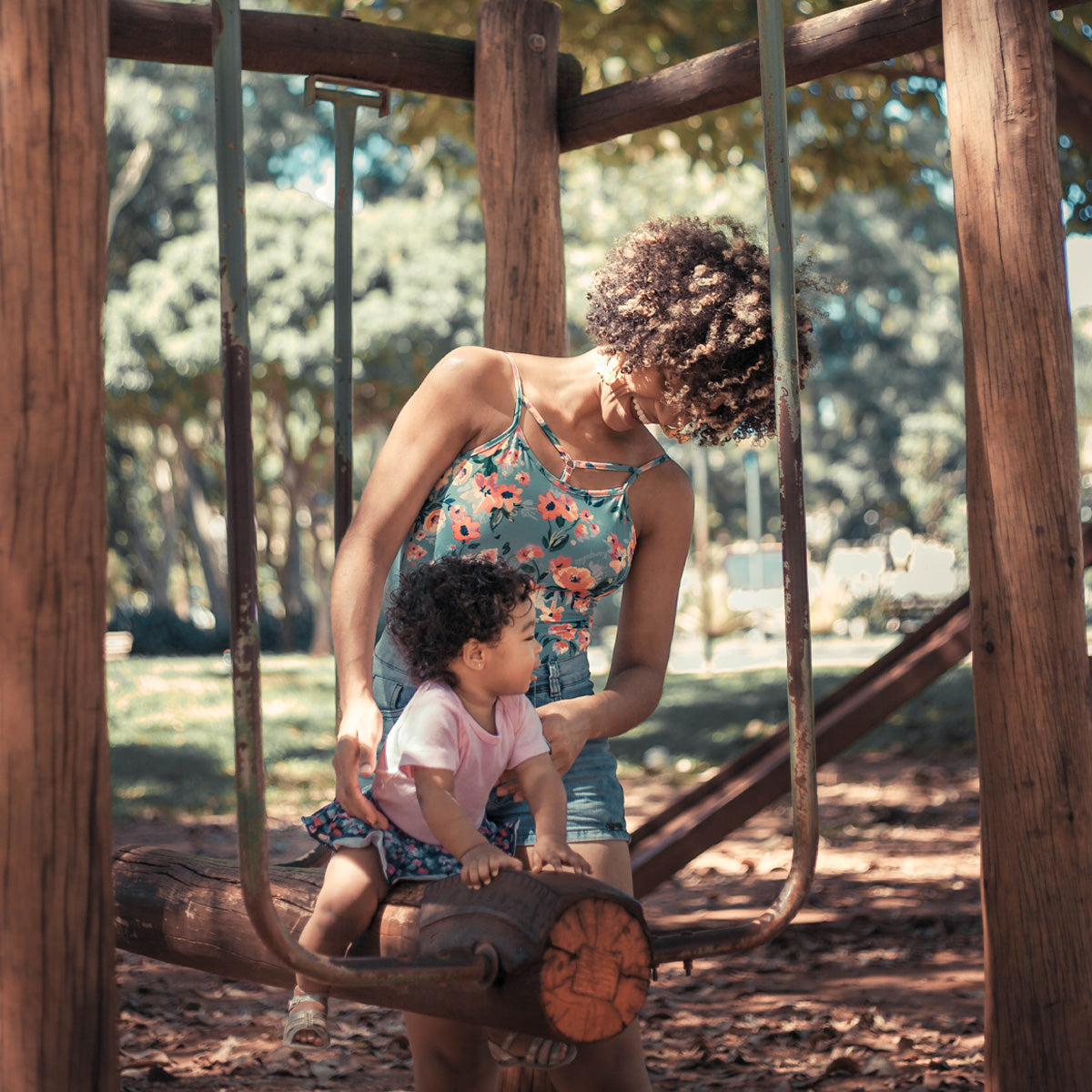 Mother and child playing at the park, connecting with nature.