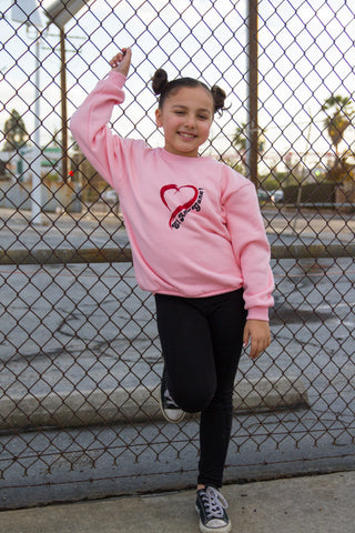 "girls pink sweatshirt with heart logo and the words ""El Amor Gana"" in glitter print."