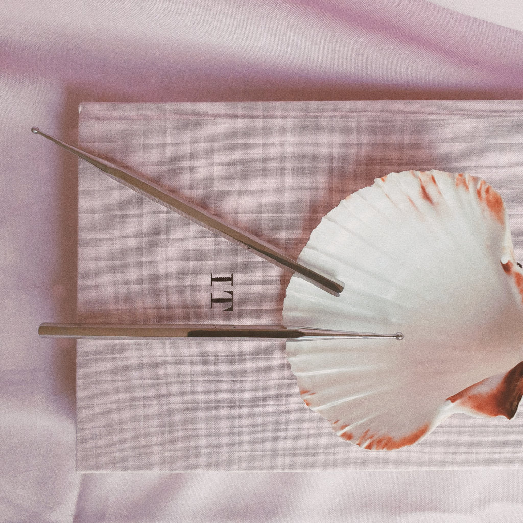 Two Facial reflexology tools on a shell with pink background