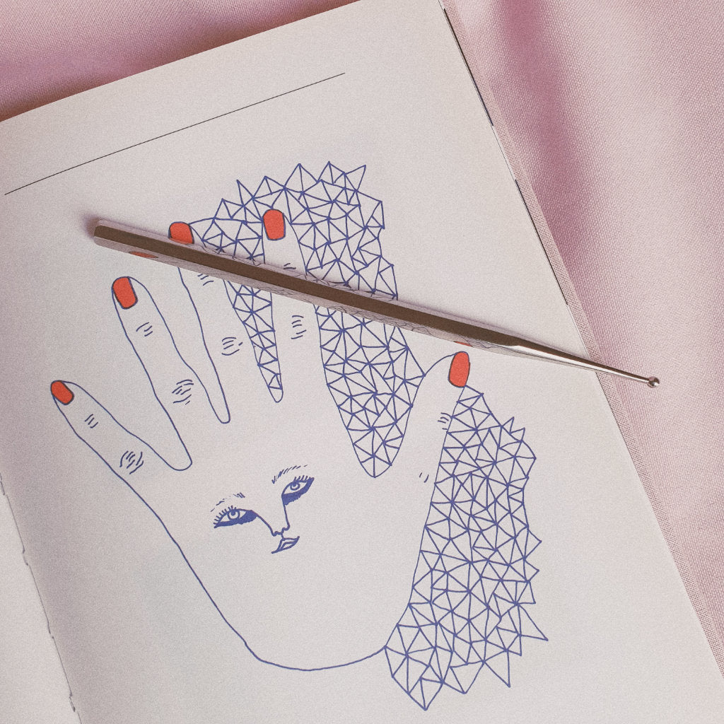 Facial reflexology tool on book opened on a drawing of a hand with face drawn on it